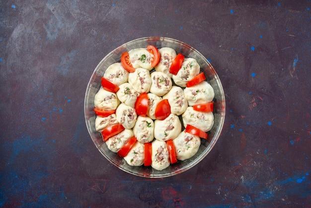 Vista dall'alto pezzi di pasta cruda con carne macinata e pomodori rossi freschi all'interno di una padella su un pasto scuro cuocere la foto a colori della cucina
