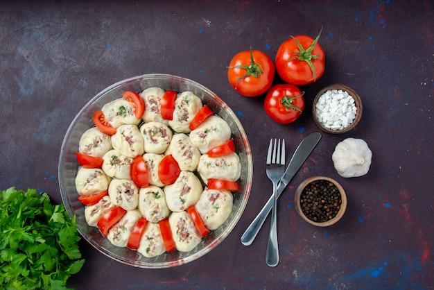Vista dall'alto pezzi di pasta cruda con verdure di carne macinata e pomodori rossi freschi sul pasto scuro cucina colore cibo foto piatto cucina
