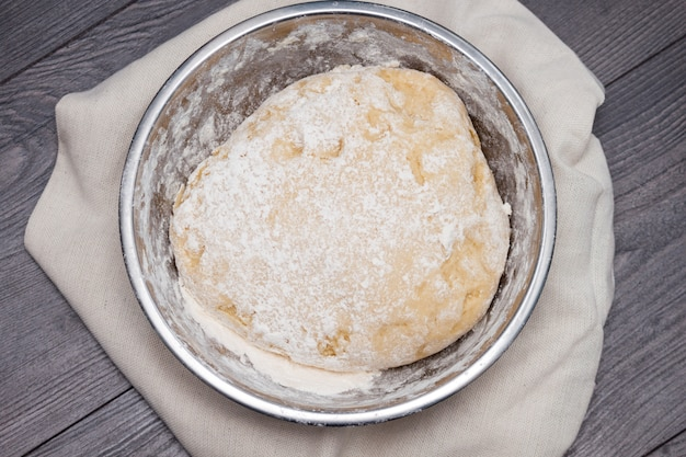 Top view of raw dough for pizza in metal plate