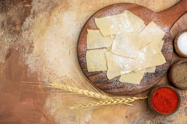 Vista dall'alto fette di pasta cruda con farina e condimenti su una superficie di legno