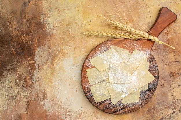 Vista dall'alto fette di pasta cruda con farina sulla scrivania in legno