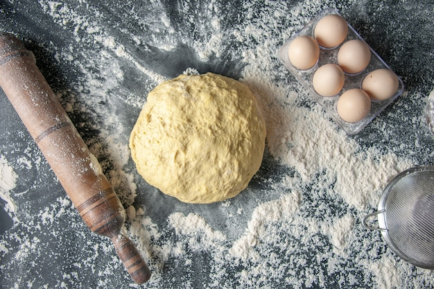 Vista dall'alto pasta cruda con uova e farina bianca su sfondo scuro pasta all'uovo panetteria hotcake pasticceria cucina cucina
