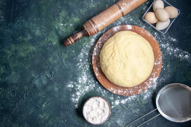 Vista dall'alto pasta cruda con farina bianca e uova su sfondo blu scuro pasticceria cuocere torta torta cruda pasta fresca al forno hotcake