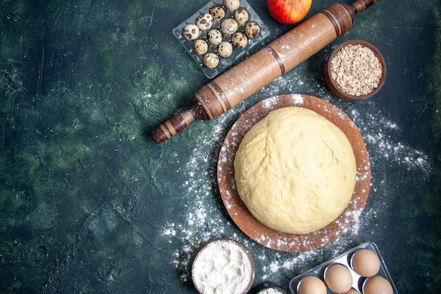 Vista dall'alto pasta cruda con farina bianca e uova su sfondo blu scuro pasticceria cuocere torta torta cruda pasta fresca al forno hotcakes
