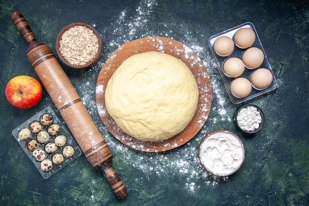 Vista dall'alto pasta cruda con farina bianca e uova su sfondo blu scuro pasticceria cuocere torta torta cruda pasta al forno hotcake