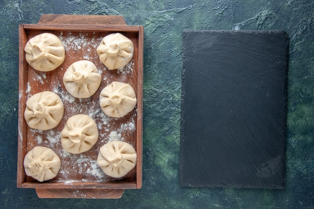 Top view raw dumplings with meat inside on dark background color meal dough meat flour dish cooking