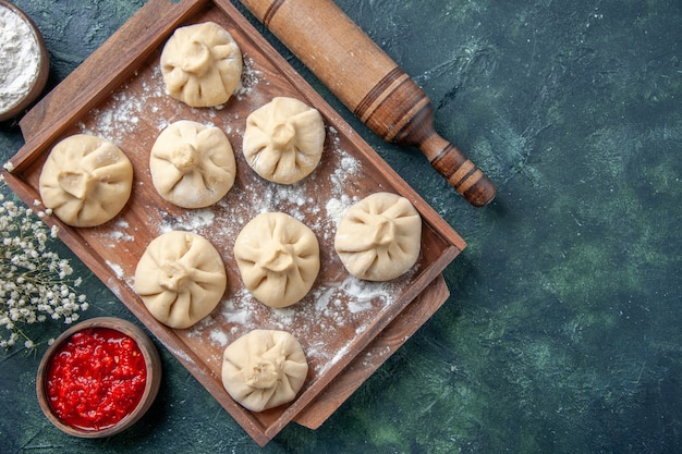 Top view raw dumplings with meat inside on a dark background meal cooking color flour pepper dish dough meat