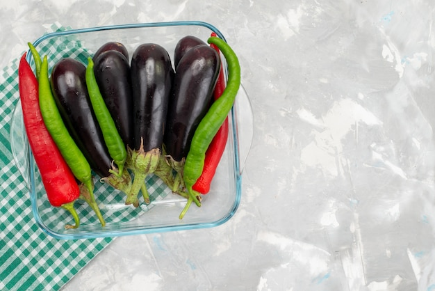 Top view raw eggplants with colored peppers on the bright desk vegetable food meal
