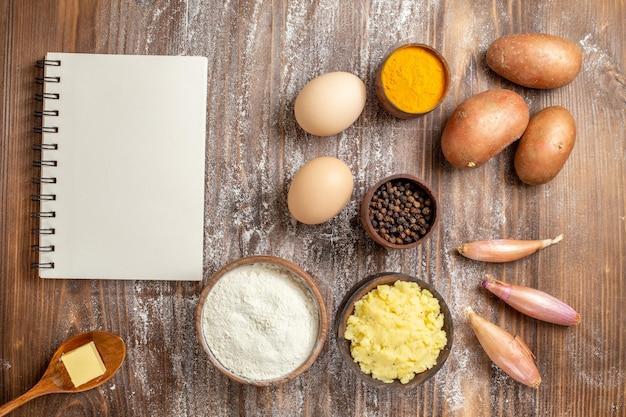 Vista dall'alto uova crude con condimenti verdure e farina su scrivania in legno pasta di farina cruda cibo