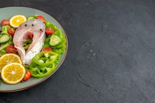 Vista dall'alto di pesce crudo e verdure fresche tritate fette di limone spezie su un piatto grigio e posate sul lato destro sulla superficie nera