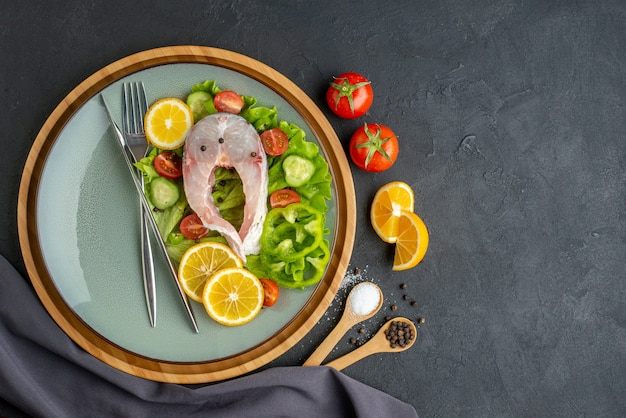 Vista dall'alto di pesce crudo e verdure fresche fette di limone e posate su un piatto grigio spezie asciugamano di colore scuro sul lato sinistro sulla superficie nera
