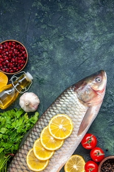 Вид сверху сырой рыбы, зелени, помидоров на столе
