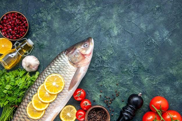 Вид сверху сырой рыбы перец измельчитель помидоры дольки лимона на столе свободное пространство