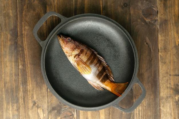 Vista dall'alto di pesce crudo sulla piastra