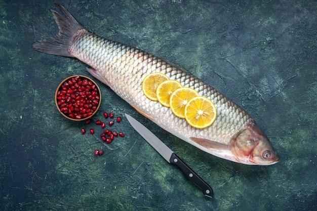 Vista dall'alto di semi di melograni di pesce crudo nel coltello della ciotola sul tavolo