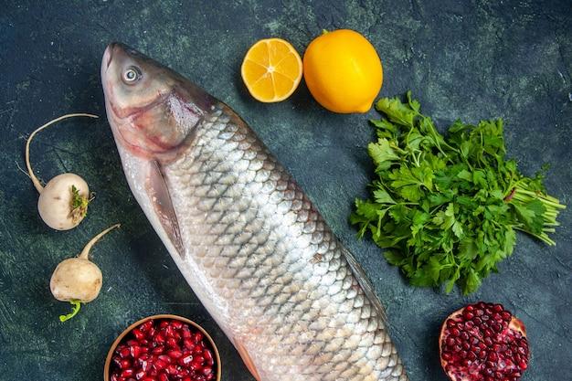 Vista dall'alto pesce crudo ravanello prezzemolo melograno in una piccola ciotola limone sul tavolo
