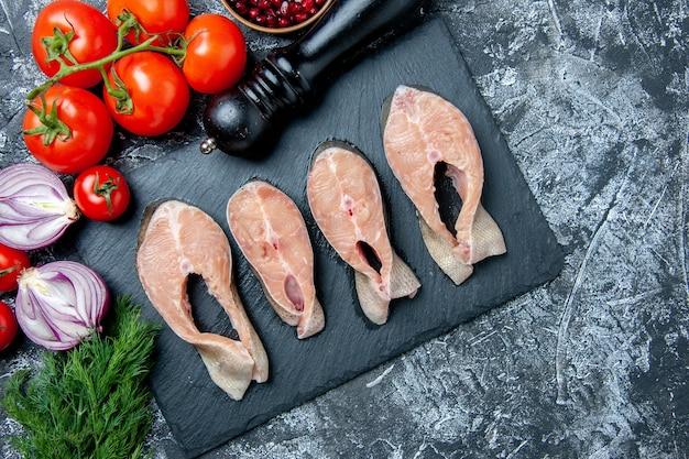 Vista dall'alto fette di pesce crudo su bordo nero aneto semi di melograno pomodori freschi macinapepe sul tavolo