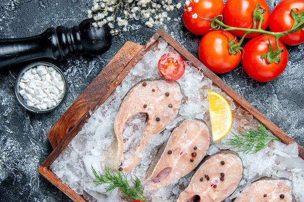 テーブルの上の小さなボウルに木の板トマト海塩の氷と上面図生の魚のスライス