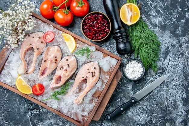 Vista dall'alto fette di pesce crudo con ghiaccio su ciotole di tavola di legno con semi di melograno sale marino aneto pomodori coltello su sfondo grigio