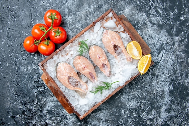 Fette di pesce crudo vista dall'alto con ghiaccio su tavola di legno pomodori freschi sullo spazio libero del tavolo