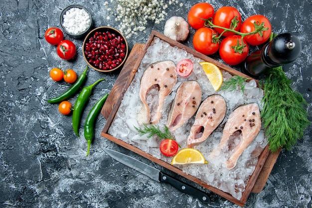 Vista dall'alto fette di pesce crudo con ghiaccio su tavola di legno ciotole di peperoncini verdi con semi di pemagranate sale marino pomodori aneto sul tavolo