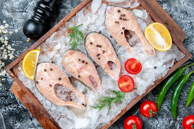 Fette di pesce crudo vista dall'alto con ghiaccio su tavola di legno pomodori macinapepe sul tavolo