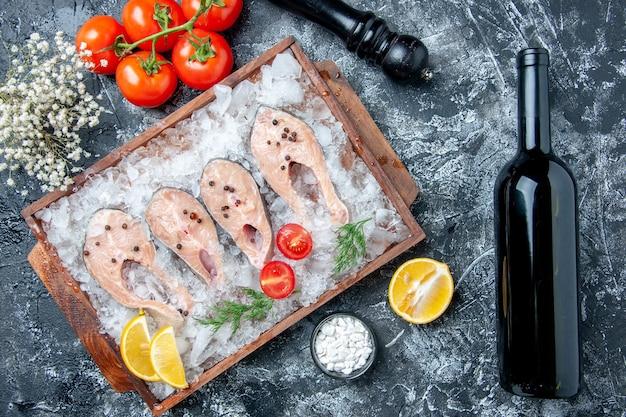 Vista dall'alto fette di pesce crudo con ghiaccio su tavola di legno pomodori macina pepe bottiglia di vino sul tavolo