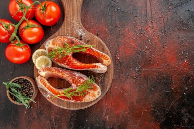 暗赤色の背景に赤いトマトと生の魚のスライスの上面図