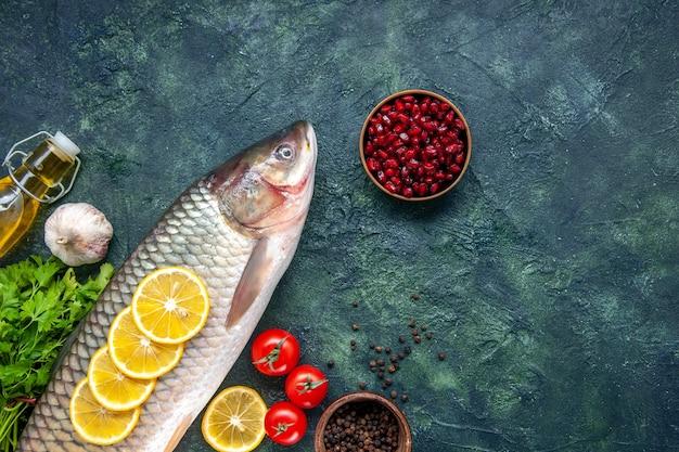Вид сверху сырой рыбы, помидоров, ломтиков лимона на столе свободное пространство