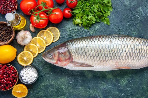 Vista dall'alto pesce crudo pomodori fette di limone sale marino in una piccola ciotola sul tavolo da cucina