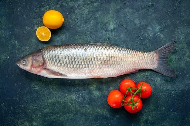 Vista dall'alto pesce crudo pomodori limone sul tavolo con posto copia