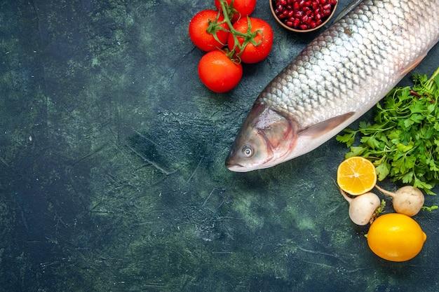 상위 뷰 생 생선 토마토 무 파슬리 석류 바다 소금 작은 그릇에 레몬 복사 장소가 있는 테이블에