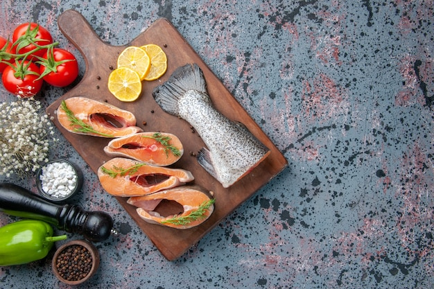 Top view of raw fishes lemon slices greens pepper on wooden cutting board and vegetables on blue black colors table