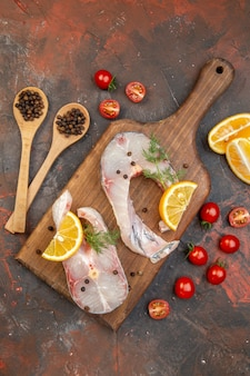 Top view of raw fishes and pepper on wooden cutting board lemon slices tomatoes on mix color surface