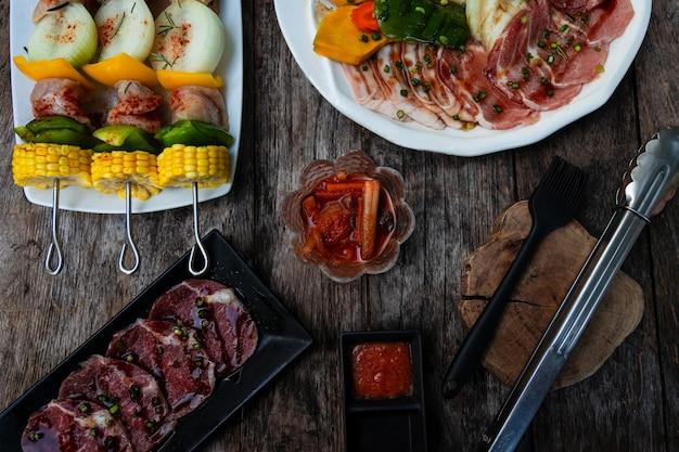 톱 뷰 한국식 구운 고기와 바베큐를 만들기 위한 원시가 나무 테이블에 놓여 있습니다.
