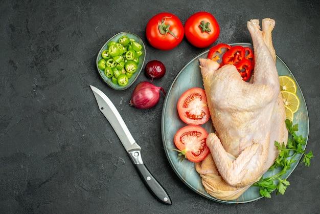 暗い背景に緑と野菜とプレート内の生の新鮮な鶏肉の上面図
