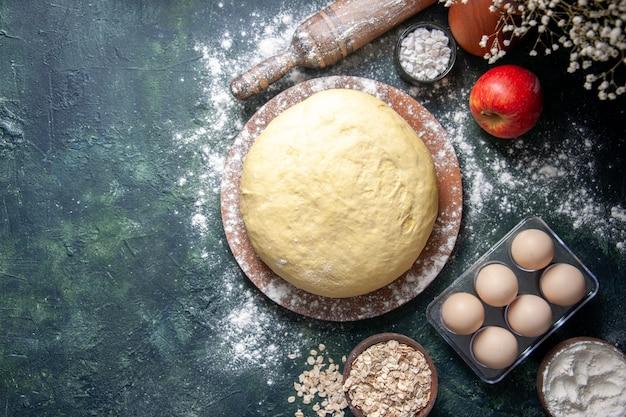 Vista dall'alto pasta fresca cruda con uova su sfondo scuro pasticceria cuocere torta pasta cruda torta forno fresco