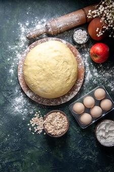 Vista dall'alto pasta fresca cruda con uova su sfondo scuro pasticceria cuocere torta torta hotcake cruda pasta fresca al forno