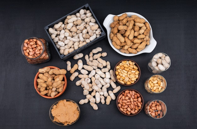 Top view raw, fresh, fried peanuts and peanut butter in box, jar and bowl, on dark