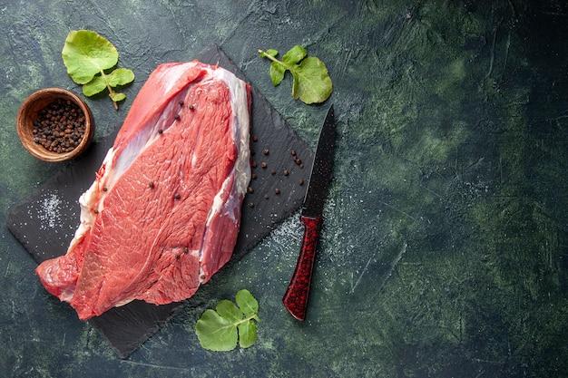 Vista dall'alto di carne rossa fresca cruda su tagliere pepe e coltello su sfondo nero verde mix di colori