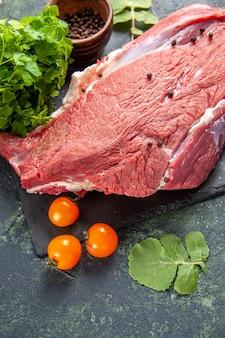 Vista dall'alto di carne rossa fresca cruda sul tagliere pomodori pepe su sfondo nero verde colori mix