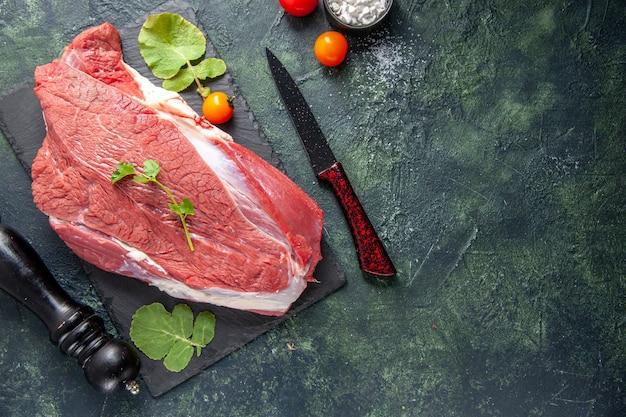 Vista dall'alto di carne rossa fresca cruda e verdure su tagliere coltello pomodori martello di legno su sfondo nero verde colori misti