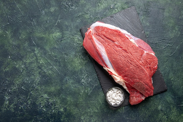 Vista dall'alto di carne rossa fresca cruda e sale sul tagliere su sfondo di colori misti nero verde
