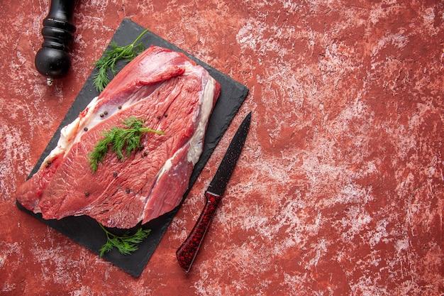 Vista dall'alto di carne rossa fresca cruda con verde e pepe su coltello da tavola nero martello di legno su sfondo rosso pastello ad olio con spazio libero