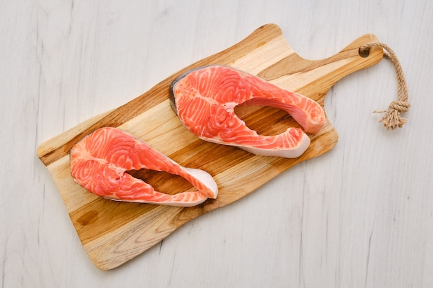 Top view of raw fresh salmon steak on wooden cutting board
