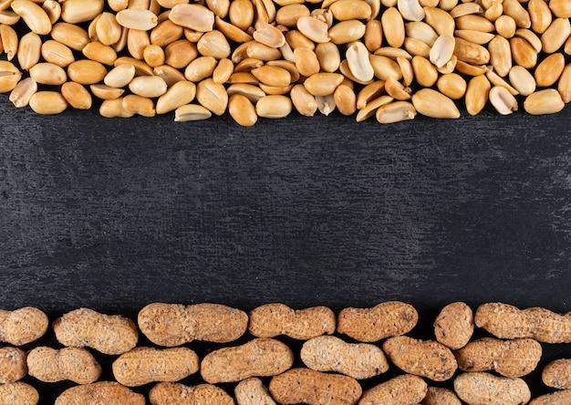 Struttura delle arachidi crude e fritte di vista superiore con lo spazio della copia nel centro sul nero