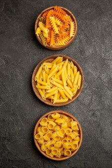 Vista dall'alto pasta italiana cruda diversa formata all'interno di piatti su grigio