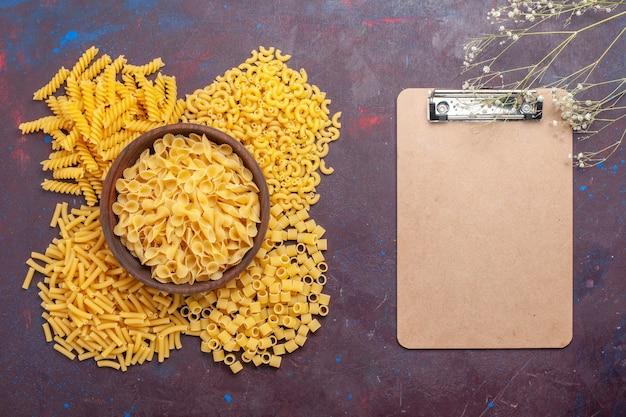 Vista dall'alto pasta italiana cruda diversa formata poca pasta con blocco note su sfondo scuro cibo crudo pasta italiana colore del pasto