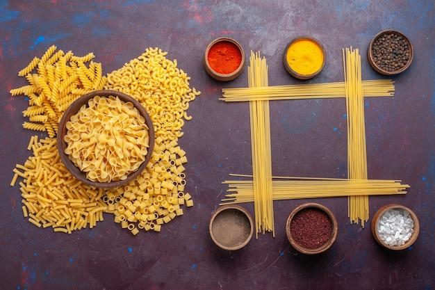 濃い紫色の背景に調味料で形成された異なるイタリアの生パスタの上面図成分食品食事生