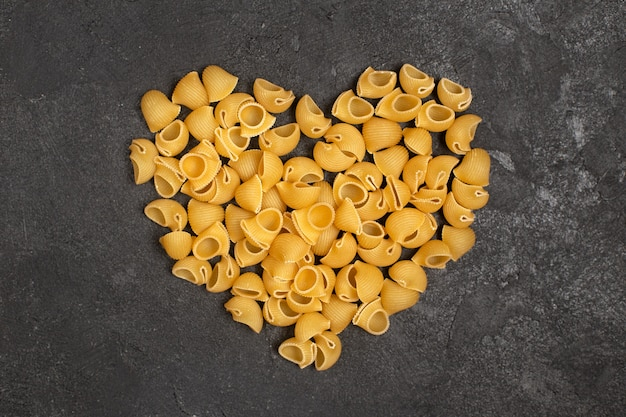 Top view of raw italian pasta forming heart shape on the dark surface